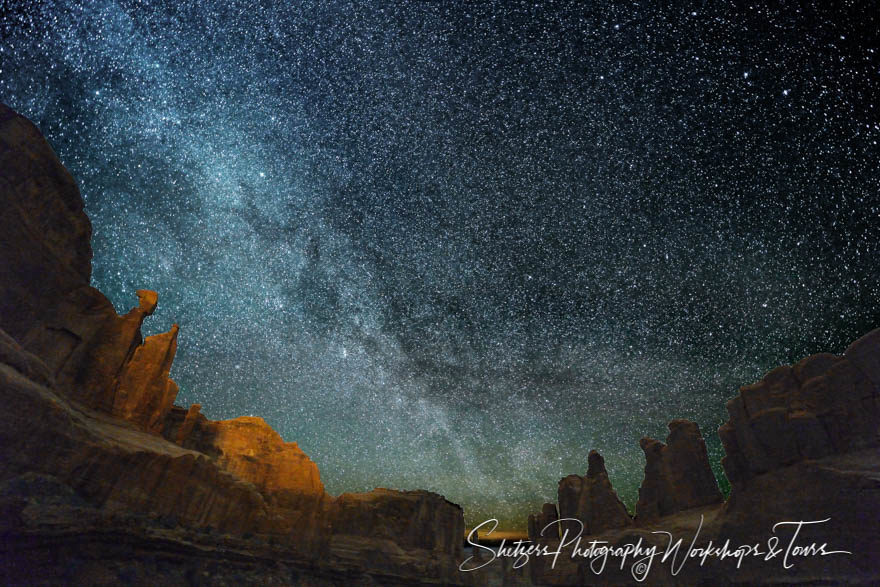 Milky way lights up Park Avenue in Arches National Park.